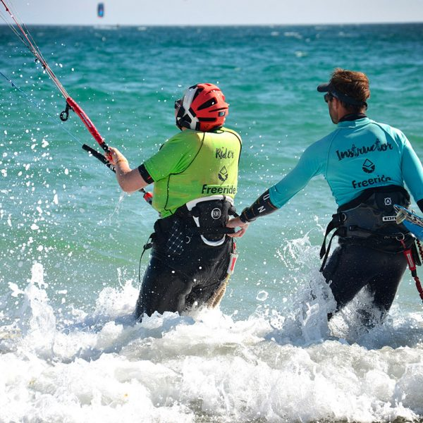 Kitesurf instructor helping his student in the water