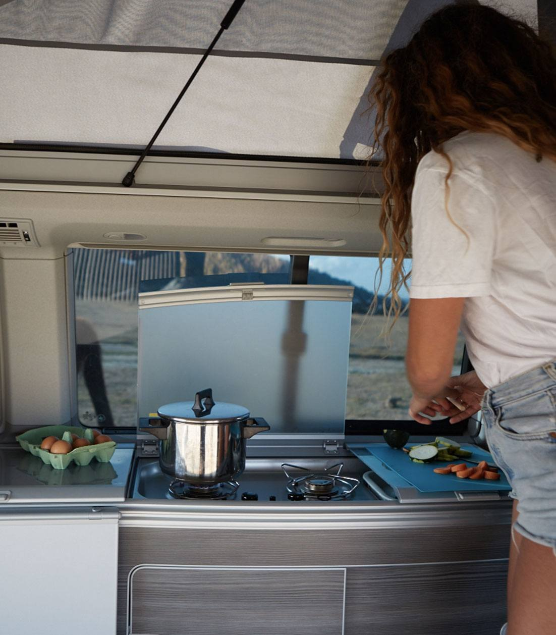 Woman cooking vegetables inside a campervan kitchenette