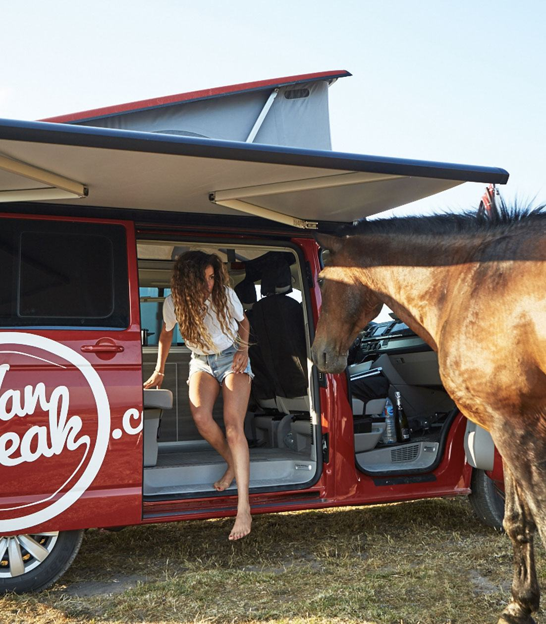 Woman stepping out of a red campervan in front of a horse