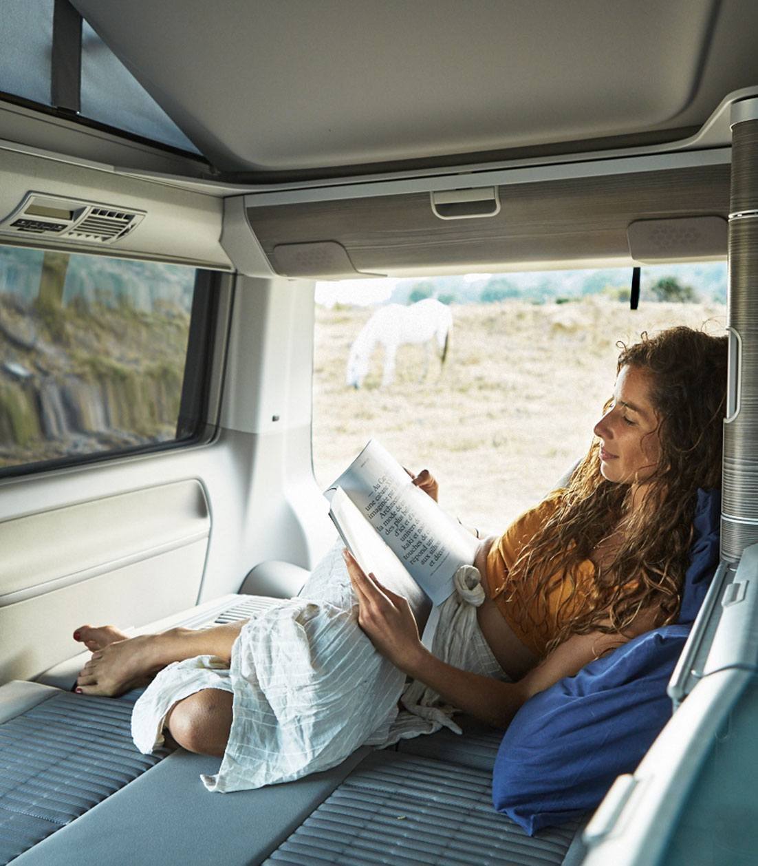 Curly haired woman reading inside a campervan
