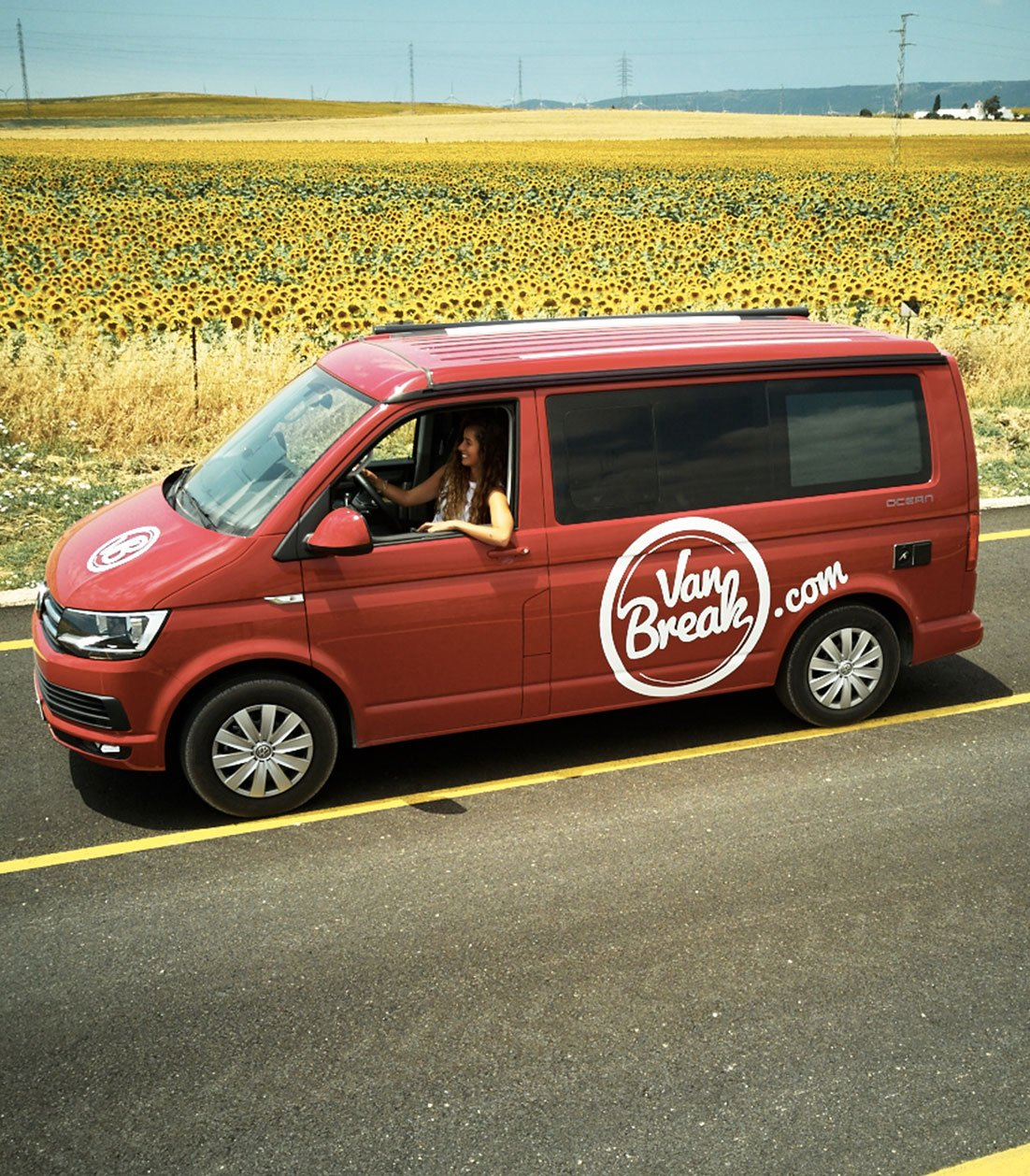 Woman driving a red Campervan VW on a roadtrip